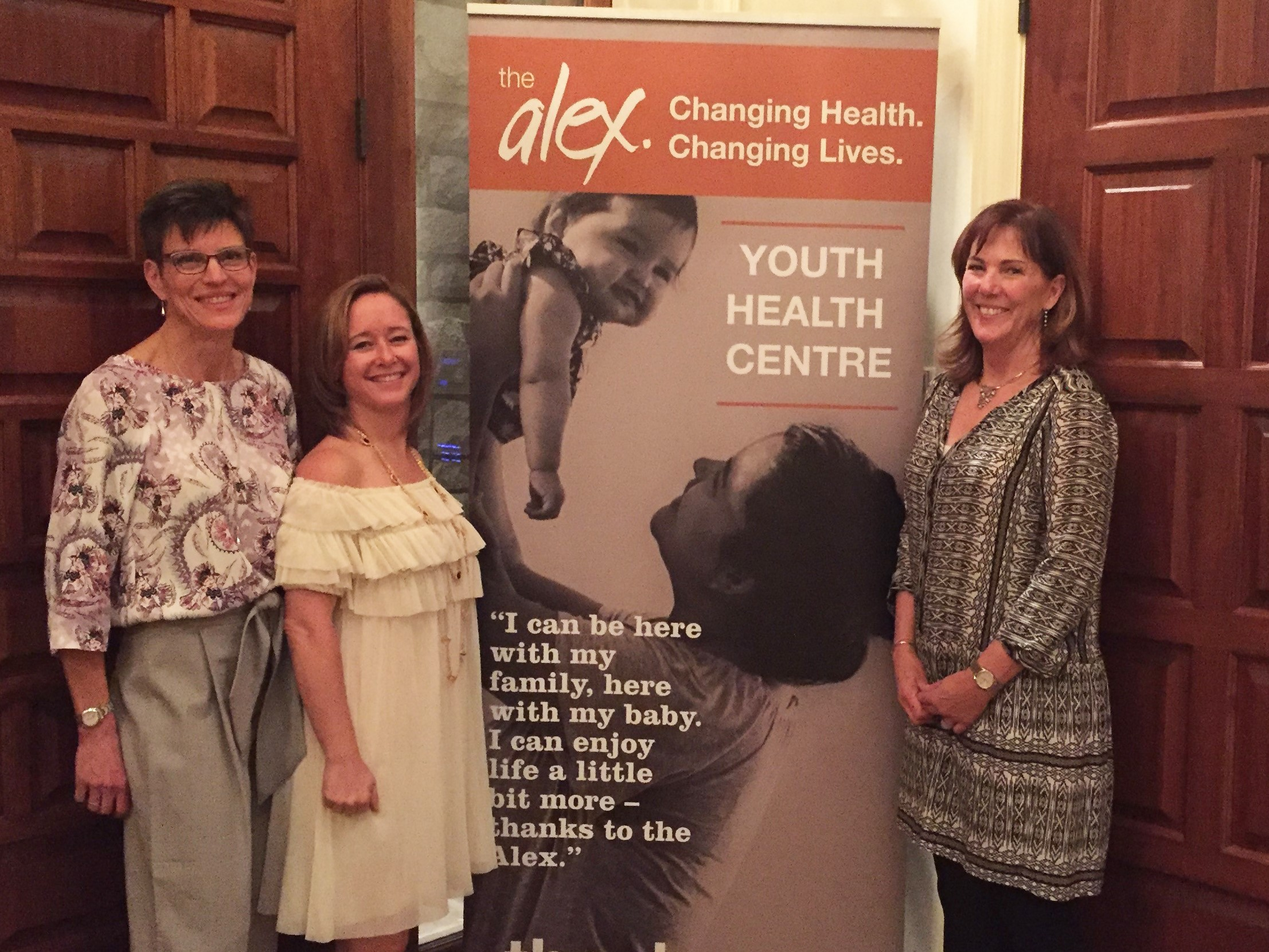 three women standing in front of an Alex Youth Health Centre banner