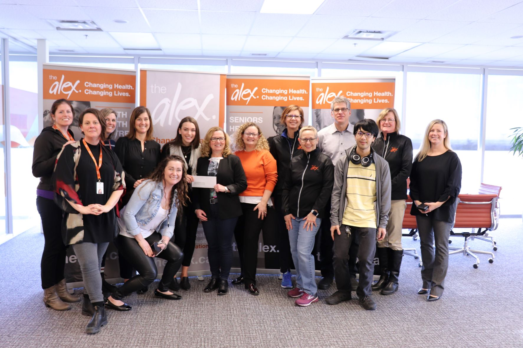 Group of Alex staff and donors smiling for a photo during a check presentation