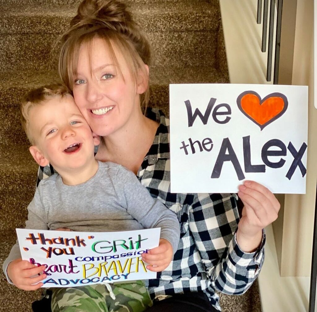 """Mother and child holding signs that say """"We love The Alex"""""""