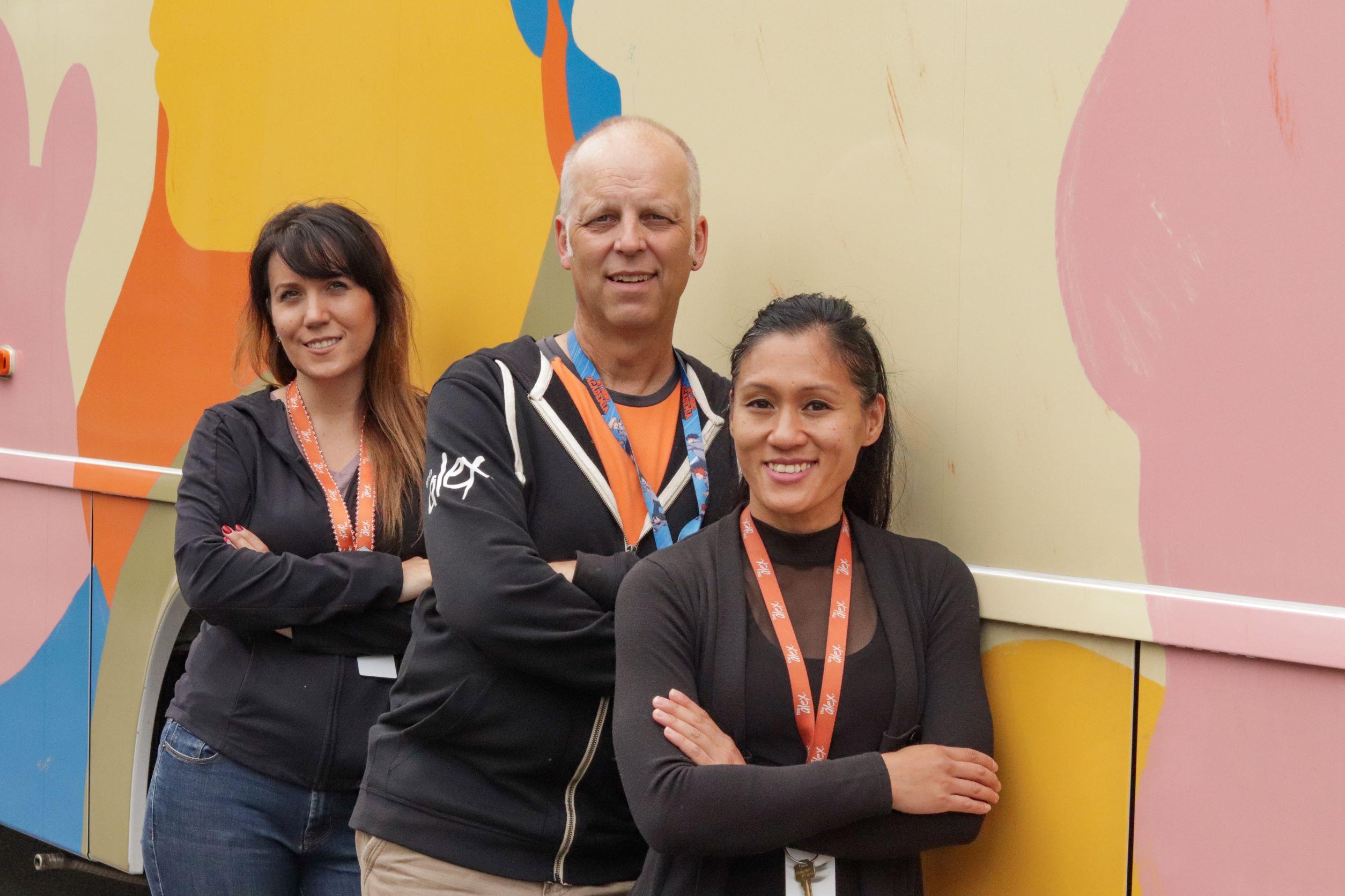 Three Alex staff stand next to The Alex Community Health Bus