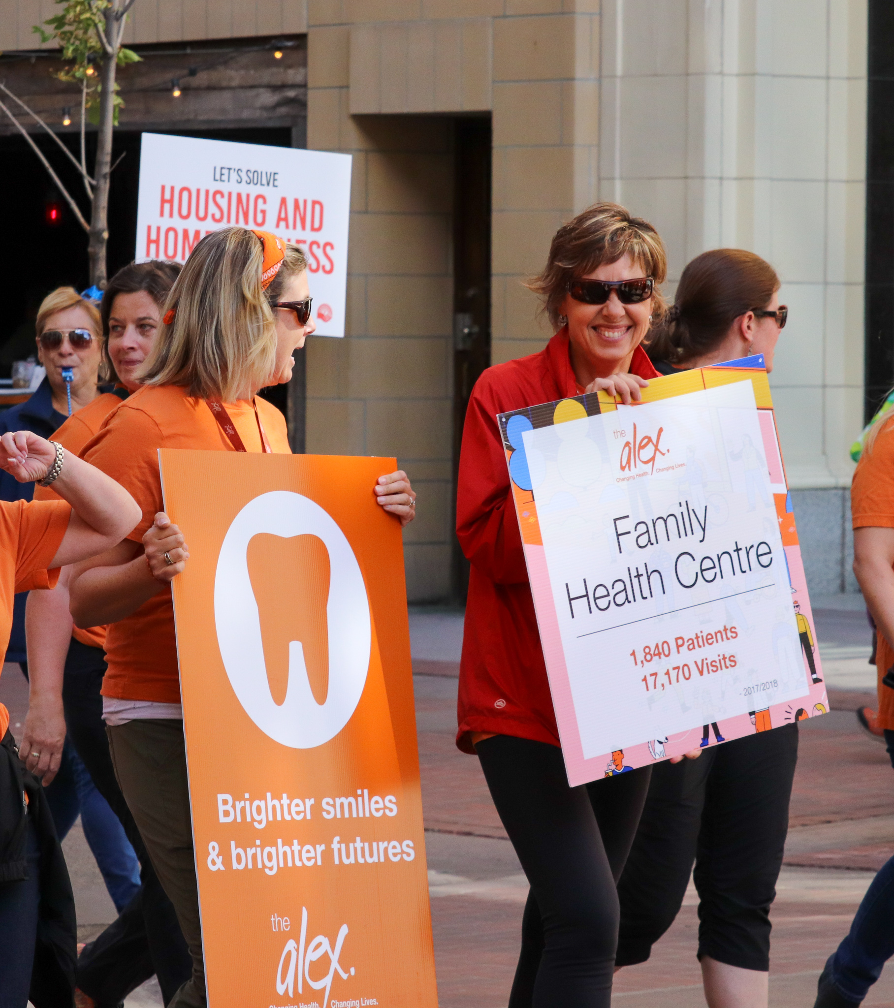 Two Alex staff walking in a parade holding signs that advertise Alex programs