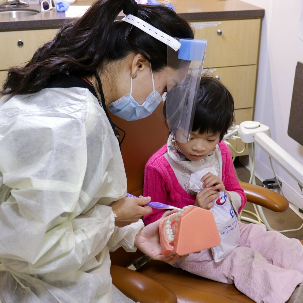 dental hygenist teaching a child how to brush properly using a model of teeth